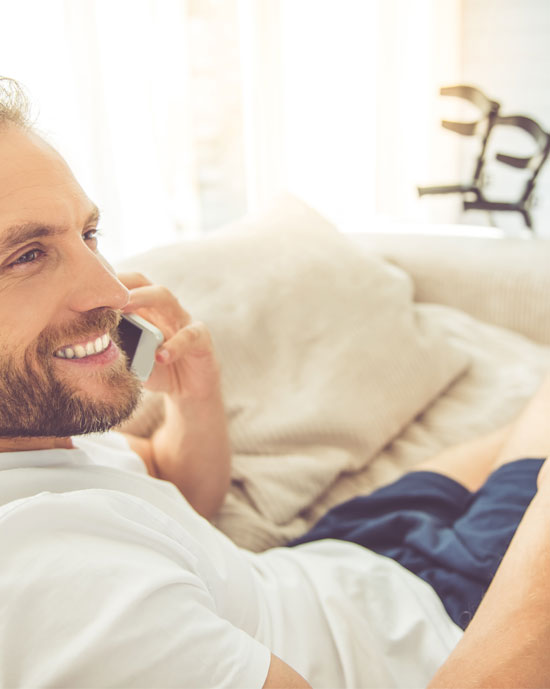 stock-photo-handsome-man-with-broken-leg-is-talking-on-the-mobile-phone-and-smiling-while-sitting-on-couch-at-495564130-mini
